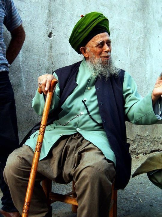Shaykh Nazim in a celadon Ottoman style shirt, navy blue waist coat and dark khaki salvar