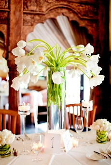 tall displays of white French tulips, with candles and additional tulip centerpieces arranged at the base