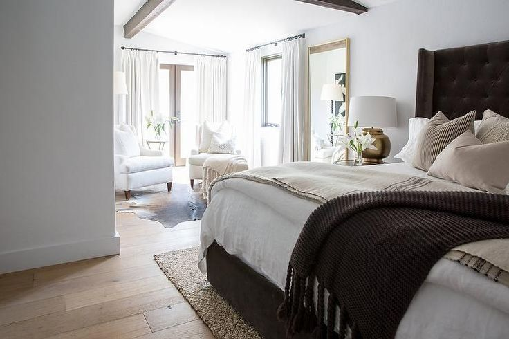 Exquisitely appointed bedroom features a jute rug placed beneath a dark brown velvet wingback bed covered in white linen bedding accented with a vintage French burlap throw blanket and a brown chunky knit throw blanket.