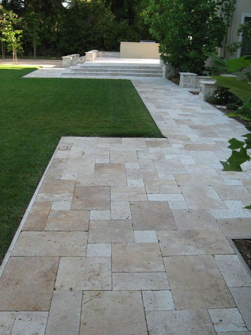 Travertine patio with seat walls, fire pit and a built-in bbq and countertop.