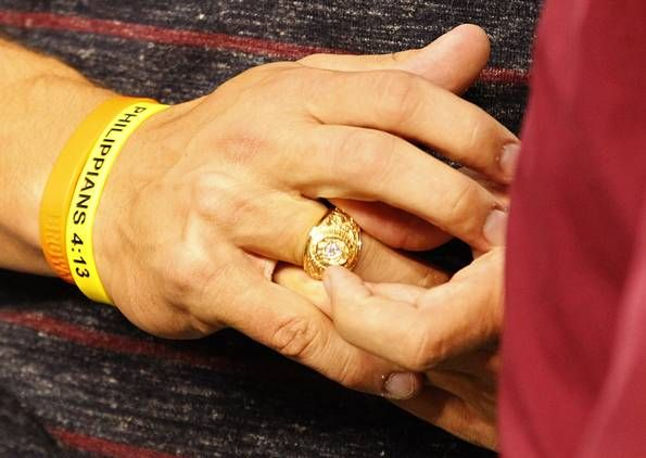 Former Texas A&M Aggies quarterback Johnny Manziel puts on his Aggie Ring after receiving it from his academic advisor Lee Hood and Portner Garner III, president and CEO of the Association of Former Students during halftime of the Southwest Classic football game between the Arkansas Razorbacks and Texas A&M Aggies at AT&T Stadium in Arlington, Texas, Saturday, September 27, 2014. (Tom Fox/The Dallas Morning News)
