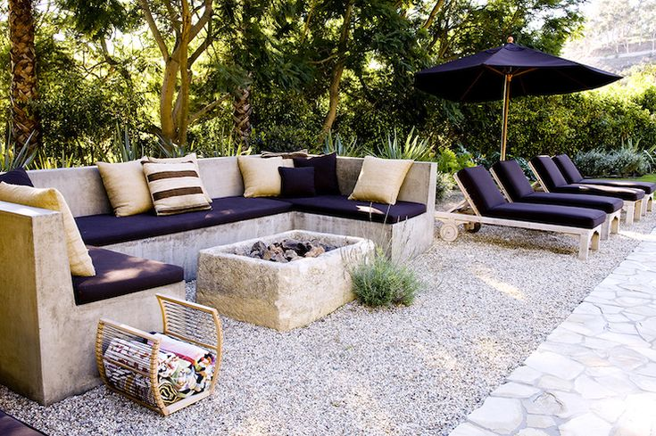 Lush patio features Ushaped outdoor concrete sofa lined