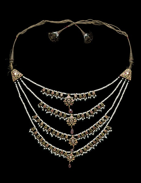 North India | Necklace consisting of 4 strings of pearls bearing enamelled gold pendants, the smaller ones set with pearls and green glass beads. The ends of the strands of pearls terminate in emerald and ruby beads, and then in enamelled plaques, which lead to tapes/strings ending in tassels. | ca. 19th century