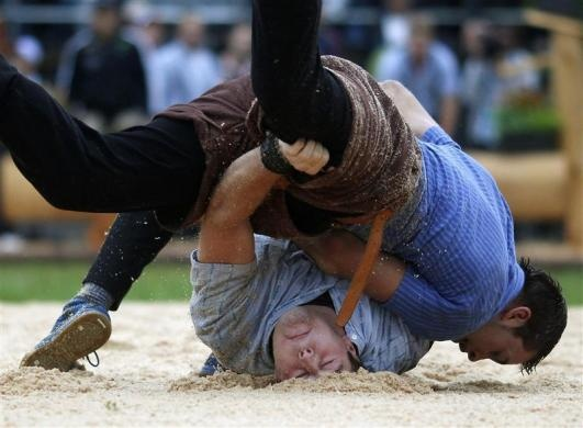 Swiss Alpine wrestler Ruedi Roschi (top) fights in a ring against Tobias Riget during the Unspunnen festival in Interlaken, Switzerland September 4, 2011. The festival, which was last held in 2006, sees people celebrating Swiss traditions by competing in Alpine wrestling and stone throwing.  REUTERS/Ruben Sprich