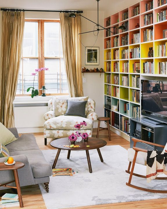 This modern floor-to-ceiling bookshelf is organized in a colorful pattern, bringing brightness to the living room.