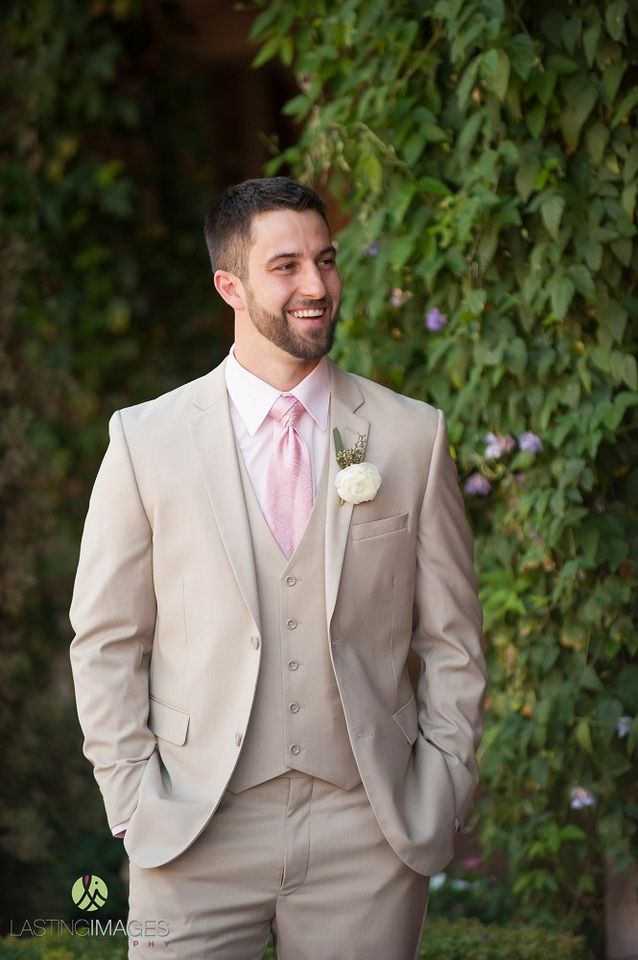 Groom poses in his khaki, three piece suit with light pink tie | Lasting Images Photography | villasiena.cc
