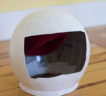 Astronaut helmet - Papier mache over a balloon, cut out face, embroidery hoop on bottom, white duct tape. (Author included a beanie inside to keep the helmet steady.)