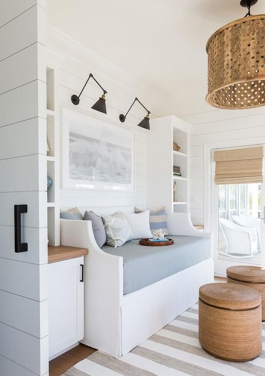 Fixed to a white shiplap wall between white built in shelves mounted over white cabinets with a wood countertop, gold and black swing arm sconces illuminate a white slipcovered daybed dressed in blue bedding accented with white and blue pillows.