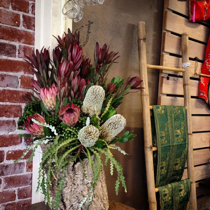 Large-scale floral arrangement for event. Proteas, Banksia, Brunia, Safari Sunset and Rainbow leucadendron. Made in a Cork Oak hollowed-out log. Flwers and foliage from Resendiz Brothers Protea Arm in Fallbrook, CA. #cagrown #fleurie