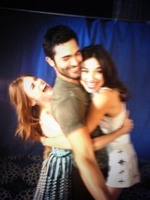 Holland Roden (Lydia) and Crystal Reed (Allison) hugging Tyler Hoechlin (Derek) behind the scenes of Teen Wolf.