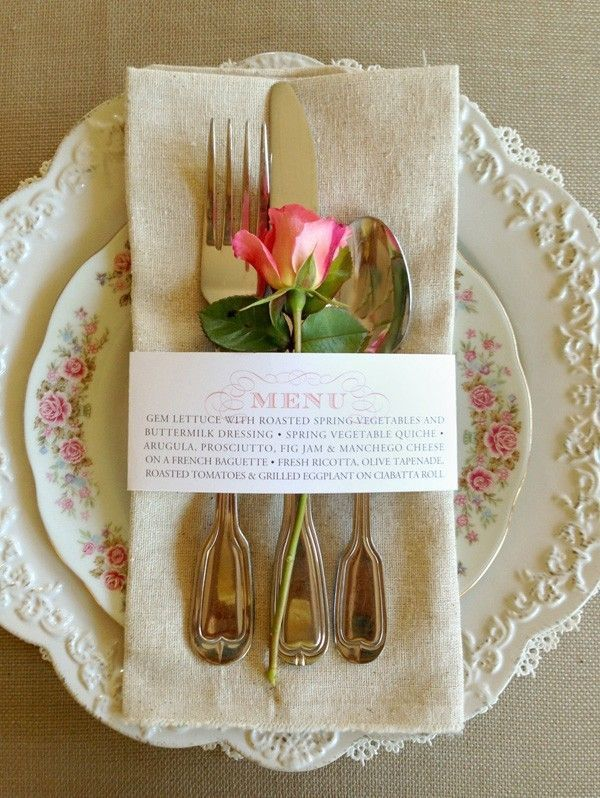 For your wedding reception, use napkins that correspond with either your tablecloth or runner. This flax napkin matches the tablecloth and ties together the pink floral decor elements. The rectangular fold and menu napkin ring are unique details for a vintage wedding reception.