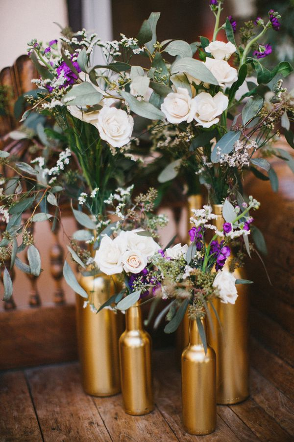 gold painted bottles, photo by Awake Photography http://ruffledblog.com/one-world-theatre-wedding #weddingideas #decor #weddingdecor