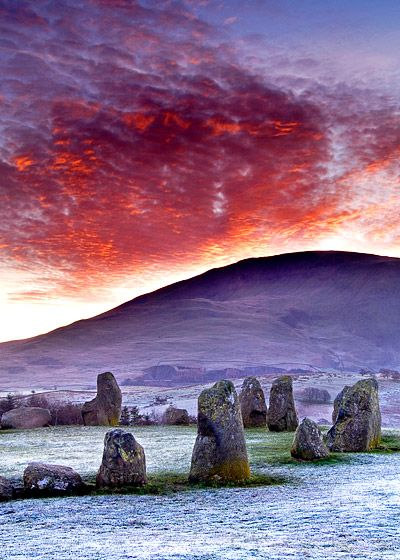 ...A very hard frost had occurred overnight turning the ground white with rime. Then as the sun rose, the thin layer of Stratocumulus cloud that was sitting over Blencathra exploded into a fiery sea of colour. Fire and Ice - a perfect combination. Location: Castlerigg situated near Keswick in Cumbria, North West England. Alan Novelli Photography.
