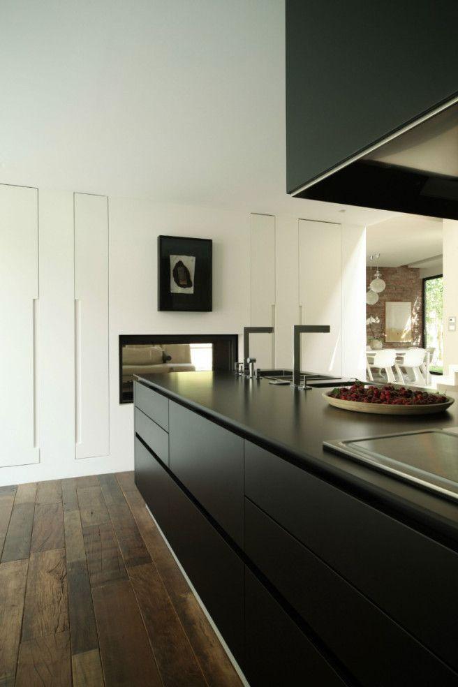 Houten vloer en zwarte strakke keuken.