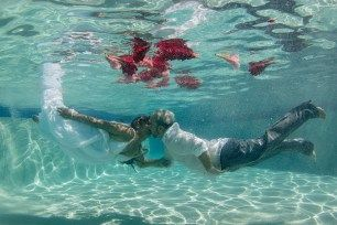 Underwater couple with flowers in the swimming pool at the Westin hotel resort in Fiji by Anais Photography