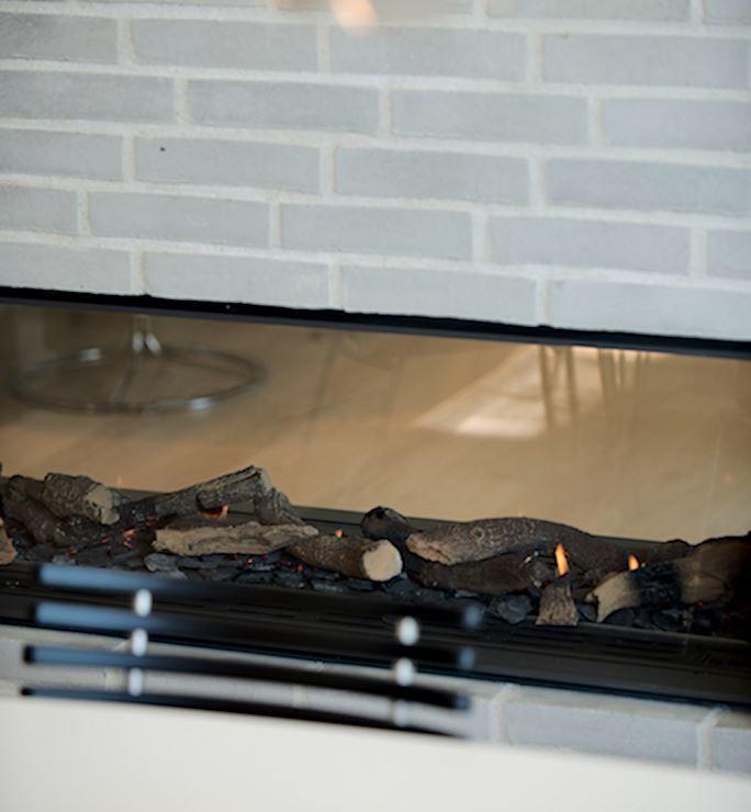 Hvis man skal udnytte sin brændeovn optimalt, skal den placeres midt i rummet. KFS Boligbyg integrere løsninger der rækker ud over det optimale - sæt glas på begge sider så du kan nyde ilden fra både køkkenet og stuen.