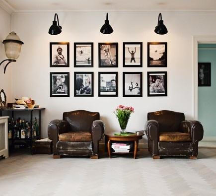 Syngga gamla läderfåtöljer vid en fotovägg