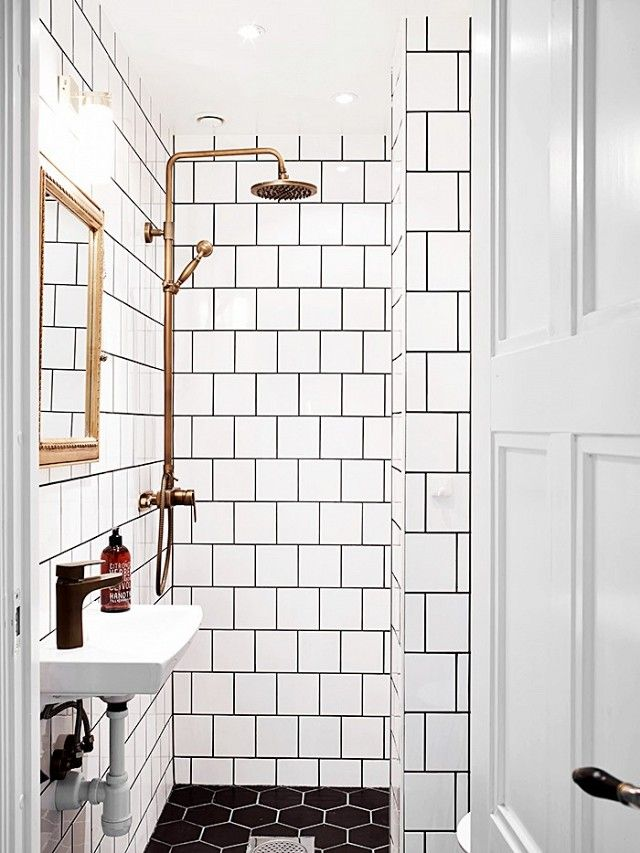 bathroom with oversize hexagonal black and white subway tiles and gold touches