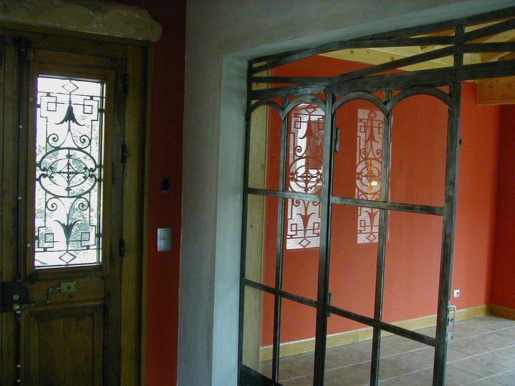 Une entrée dans laquelle on voit la porte d'entrée , et une verrière servant de cloison entre le couloir et le salon.