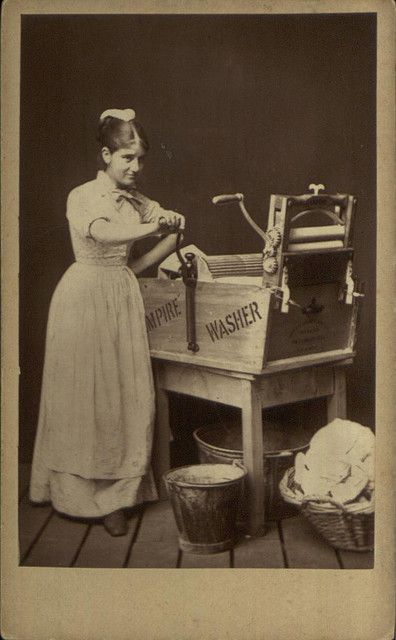 Studio composition picturing a 'laundry maid' with her mangle, pail and clothes basket, by unknown photographer, 1870-80.