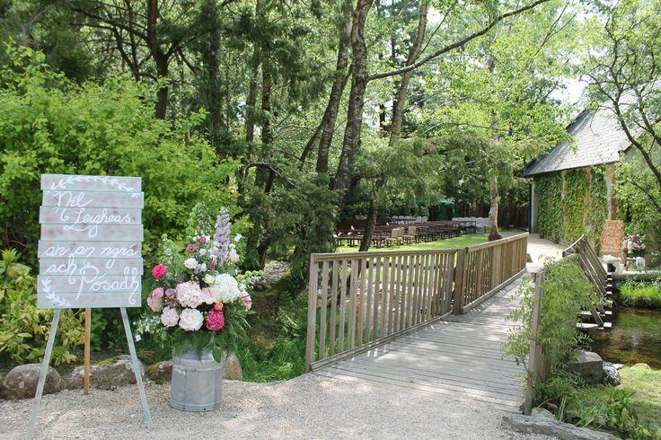 Bridge to the ceremony at Brooklodge. Irish sign and large floral arrangement