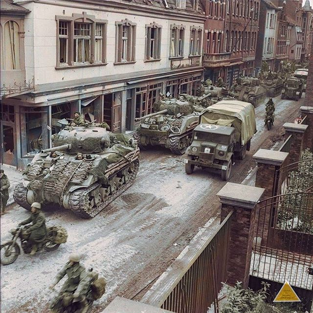 """the_ww2_archives Sherman tanks of the British 8th Armoured Brigade (possibly 4th/7th Royal Dragoon Guards) and a Chevrolet truck leading ambulances through Amsterdamerstraße in Kevelaer, North Rhine-Westphalia, Germany. 4 March 1945. Local 17 year old Kevelaer eye-witness, Heinz van Lipzig, """"My father wanted to buy a caravan and horse to move away from home and the fighting, but I was able to talk him out of this idea by telling him that the end could not be far away. I did not know what was…"""