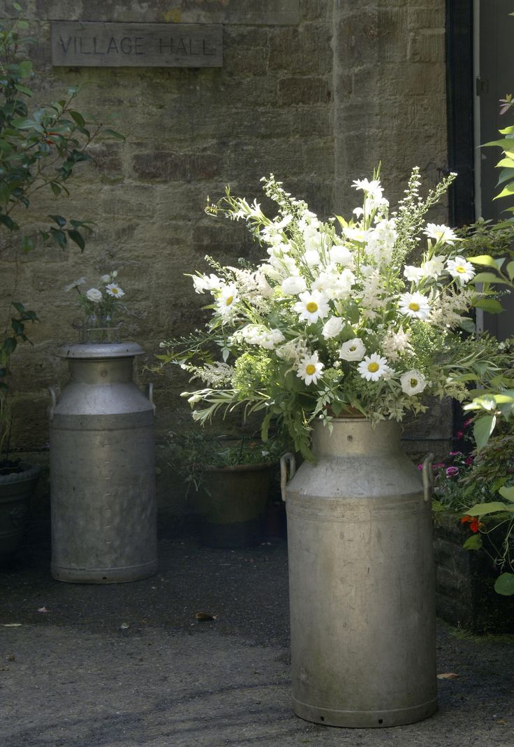Milk churns with pretty daisies welcome wedding guests. www.thelilylocket.co.uk