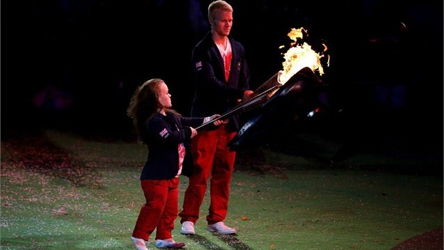 Swimmer Eleanor Simmonds and sprinter Jonnie Peacock of Great Britain light torches from the Paralympic Flame as it begins to fade  They light their Torches from the dying Flame and proceed to light various torches held by members of the Closing Ceremony cast.
