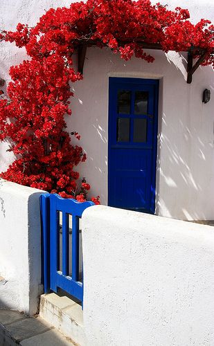 Facade with red bougainvillea and blue wooden gate. Volax, Tinos island, Cyclades, Greece