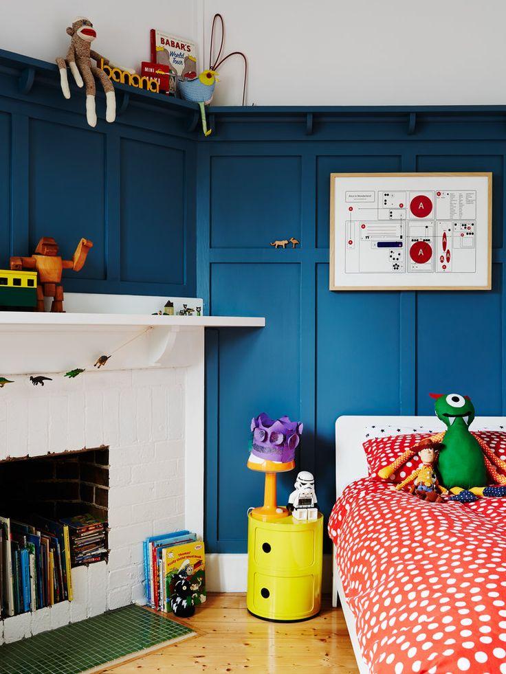 Une peinture bleu foncé et du linge de lit rouge vif dans la chambre des petits