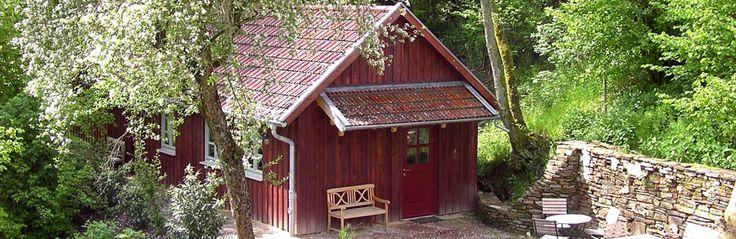 Wellness in der Bärenmühle: Saunahaus mit gemütlichem Ruheraum, in dem das Holz des Kaminofens knistert.