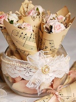 Looking for a way to incorporate music into your wedding? Try making holders out of sheet music (you can make them look antique like in the picture using tea). Put rose petals in them for after your ceremony!
