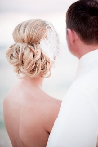 This bride's tucked up-do is gorgeous and modernized with a feather hair accessory! // Photo courtesy of Dana J. Photography.