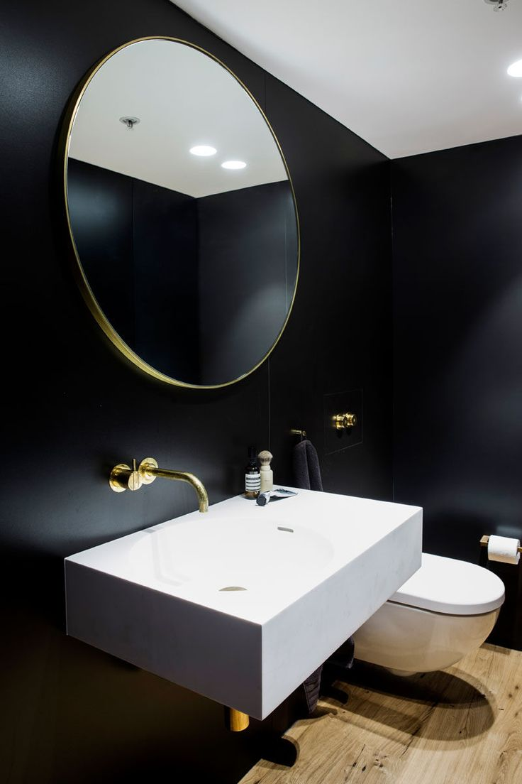This modern and dramatic bathroom features black walls, a gold framed round mirror, a gold faucet and accents, a white vanity and wooden floors.
