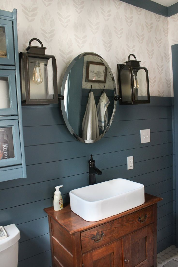 A pair of lanterns flanking a frameless mirror reflect a contemporary country bathroom. See the rest of this makeover from The White Buffalo Styling Co.