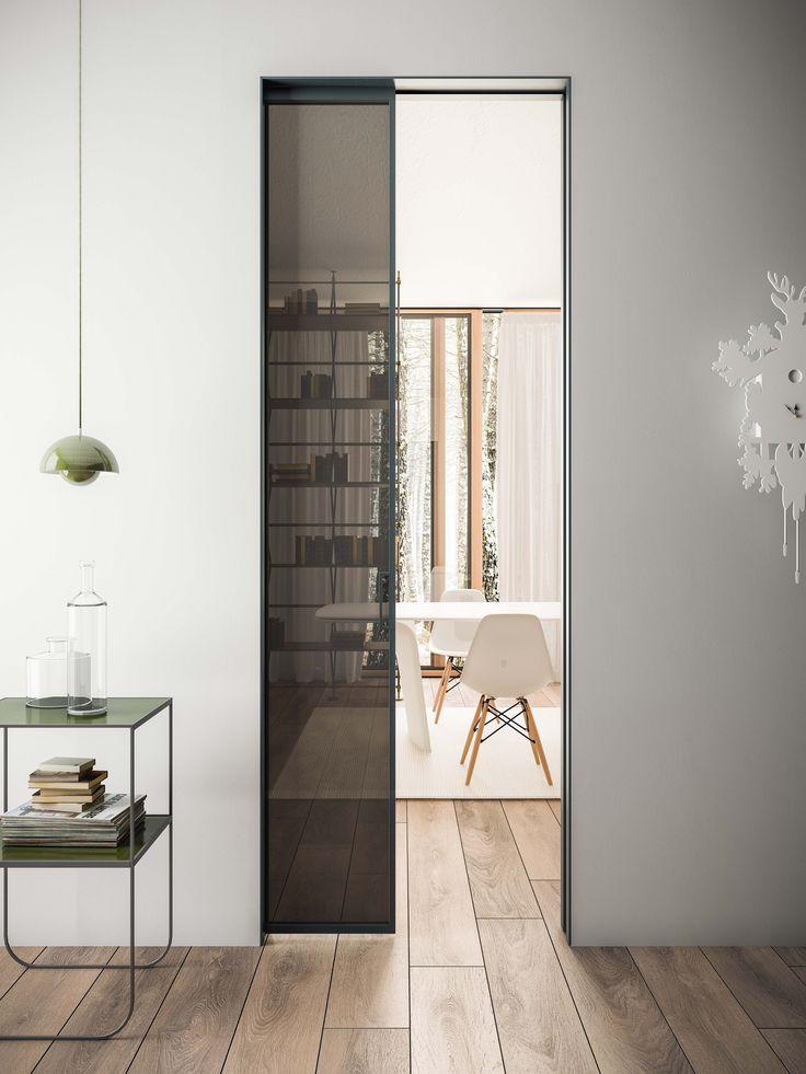 Porta scorrevole interno muro in alluminio grigio ferro e vetro fumè.