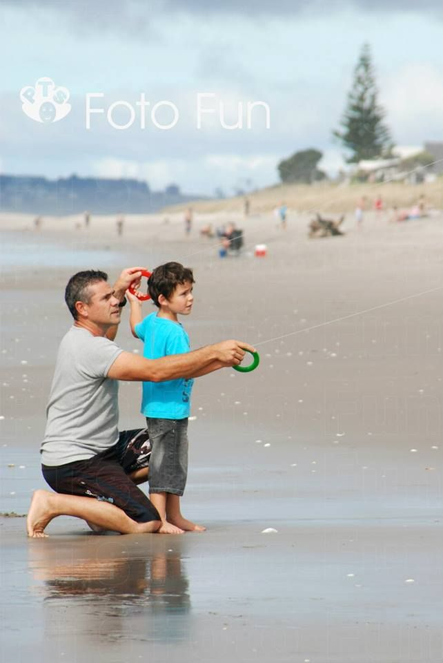 dad and son playing with kite in Papamoa beach