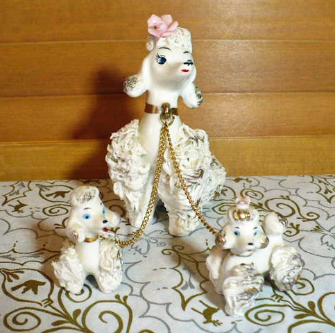 """Spaghetti poodle figurines were popular ceramic  collectibles in the 1950's. Offered is a 'mother' poodle with 'twins'- a boy and a girl in white and gilt. The fragile flowers on the heads of the mother and girl are intact as are the chains attached to the collars. The original label is intact if somewhat crumpled - """"Enterprise Exclusive, Toronto Canada"""". There is a black Japan stamp on the bottom.   $39.00  http://www.etsy.com/shop/VintageatElsiesPlace"""
