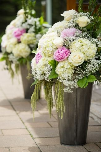 Silvertip Resort Weddings: Flowers by Janie- Calgary and Canmore Wedding Florist Ceremony Arrangements of white hydrangea, pink peonies and green hanging amaranthus at Silvertip Resort  Photo: www.ericdaigle.com Flowers: www.flowersbyjanie.com  #silvertipresortwedding #Canmorewedding #rockymountainwedding #ceremonyfloralinspiration #pinkpeonies #FlowersbyJanie #Canmoreweddingflorist #Banffweddingflorist