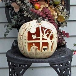 A fancifully carved pumpkin shows a scene -- with an owl in a tree-- as seen through a window......