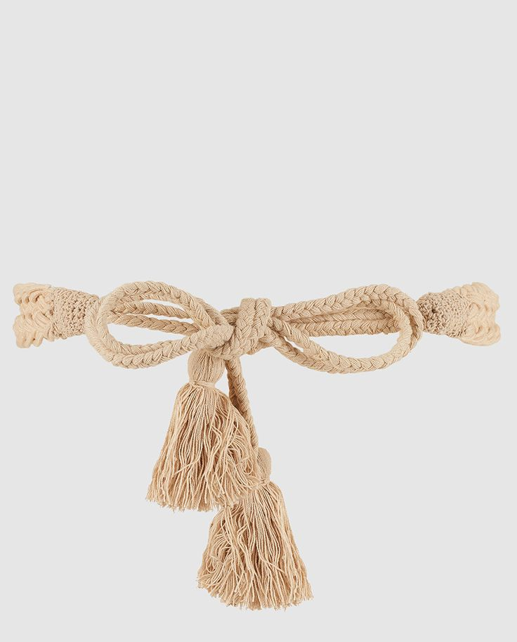 Cinturón trenzado en color beige con detalle de pompones de hilo en ambos extremos. Se ajusta mediante nudo.