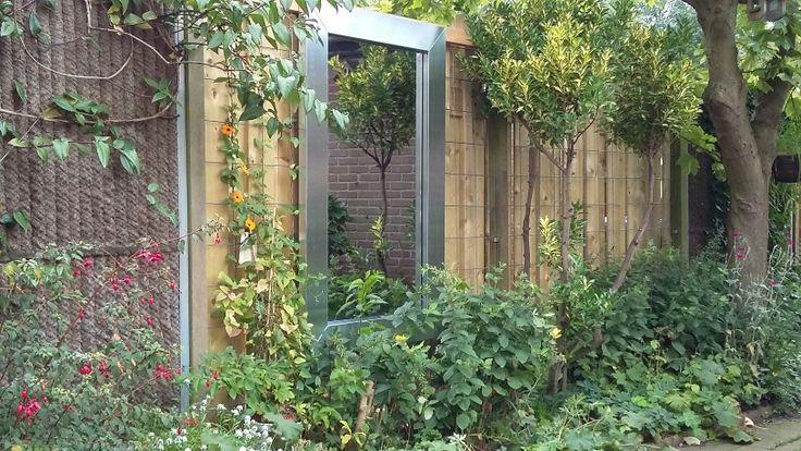 Blij mer mooie tuinspiegel met zinken rand tegen de schutting van de buren