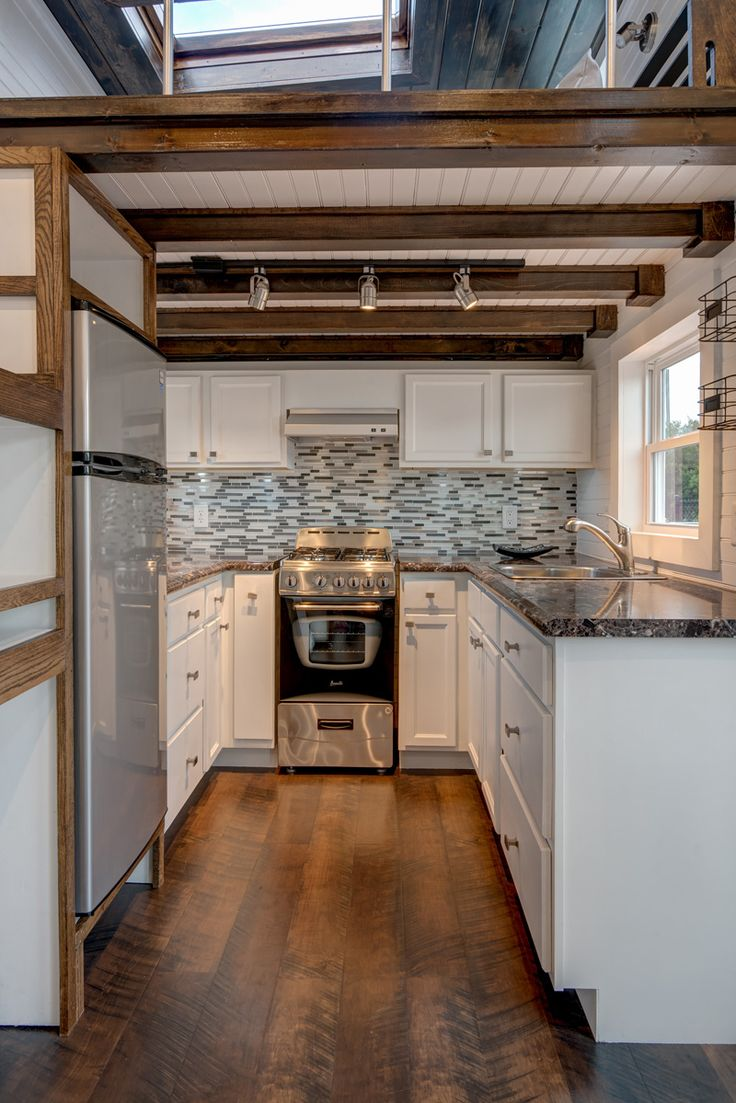 a well equipped tiny house kitchen includes a range apartment size refrigerator and upper - Tiny House Ideas