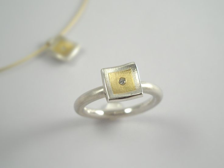 Minimal square gold and silver ring with a diamond.