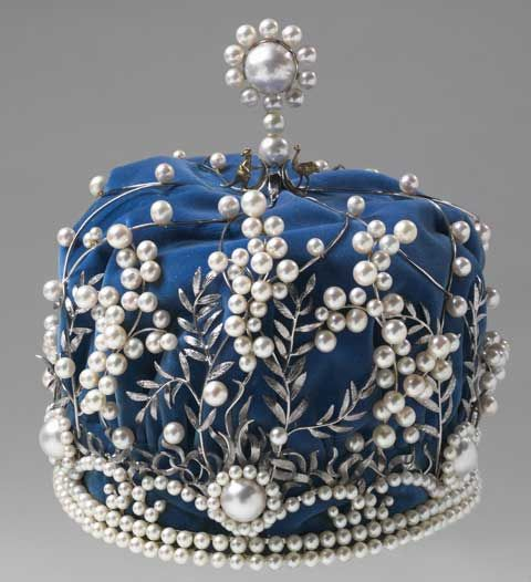 An era past - Crown with pearls as wattle flowers and silver leaves, over a blue fabric base. A silver kangaroo and emu stand either side of a larger pearl at the top of the crown.