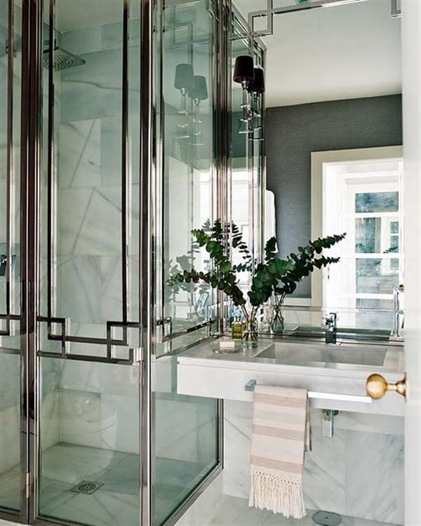 glass and metal shower door pattern and marble vanity.