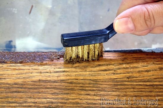 She's using a wire brush to stip old stain from the wood. - (stripping tutorials at http://www.sawdustandembryos.com/tutorials )
