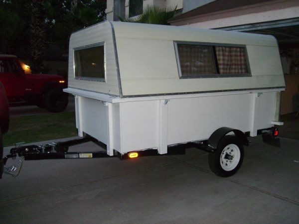 I needed to save this pic.  I like how he took a utility trailer, put a camper on the back and hauls it with his SUV.  He has cute curtins on the inside and said he puts his camping gear in back then sleeps on a inflated mattress bed at night.