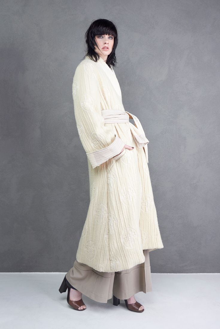 Oversize line overcoat, made of mixed wool with cuffs, neckline and belt reaized in a contrast fabric.