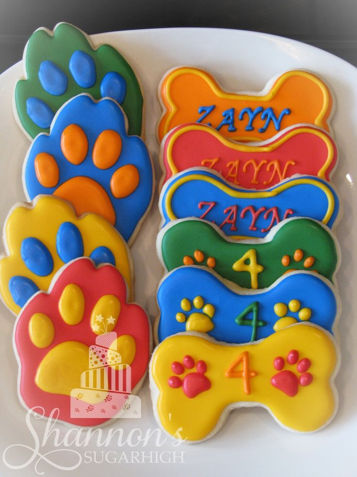 Paw Patrol theme royal icing painted shortbread cookies in the shape of dog bones and paws. Colours include blue, green, yellow, red, and orange. Keyword: Sugar cookie, children, birthday.